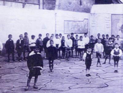 Imaxe histórica de nenos xogando nos mapas do patio do colexio
